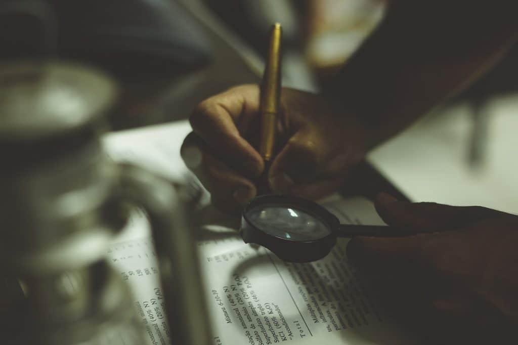 Une personne en train d'écrire consulte son texte avec une loupe.