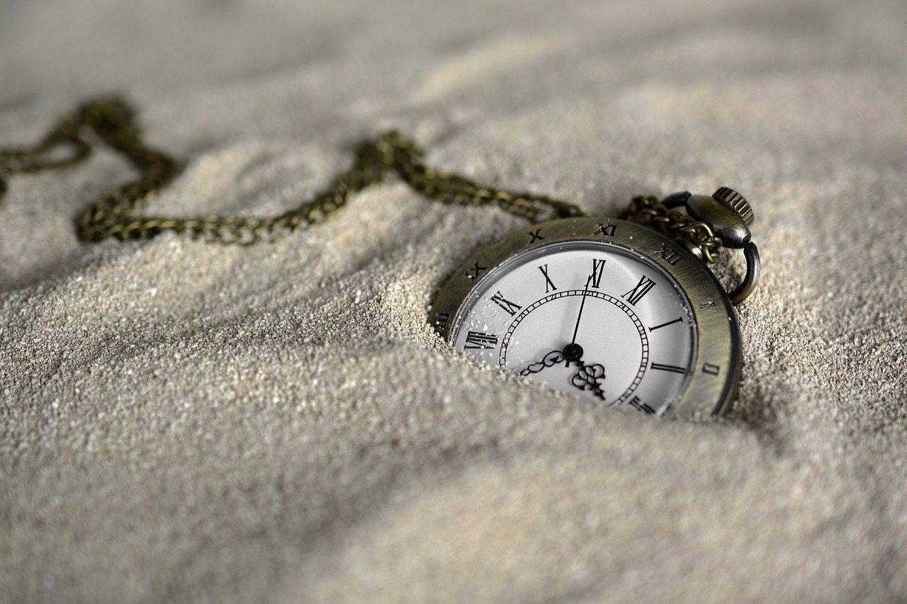 Une montre à gousset à moitié enfouie dans le sable