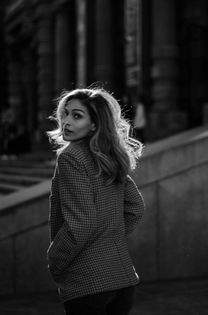 Une jeune femme se retourne vers nous, pendant sa visite guidée d'une ville européenne.
