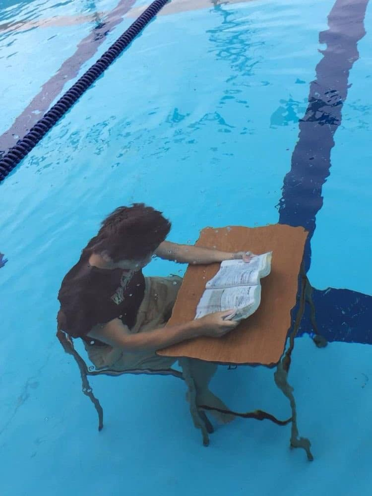 Au fond d'une piscine, une personne lit à un bureau